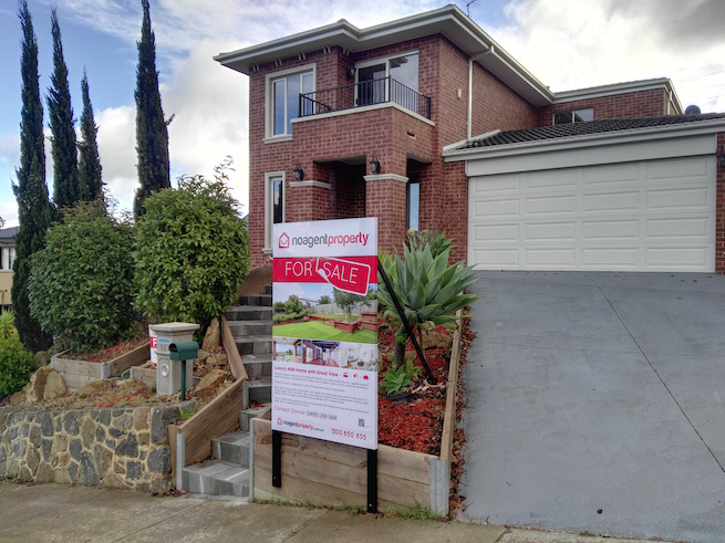 real estate photosign for sale by owner in front of a house